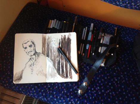 filmmaker drawing in sketchbook on train