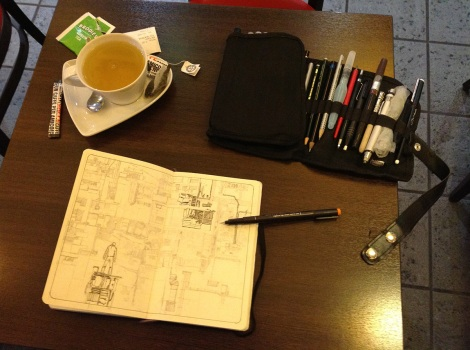 drawing a science fiction story in a Moleskine sketchbook with pen and ink in a coffee shop