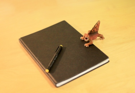 Writer artist John E. Brito´s workspace with dinosaur figure on sketchbook
